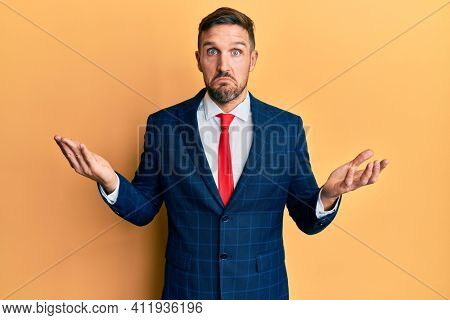 Handsome man with beard wearing business suit and tie clueless and confused expression with arms and hands raised. doubt concept.