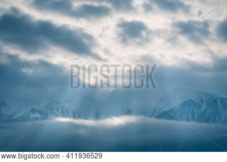 Winter Mountains Covered With Snow Between Fog Clouds With Bright Sunrays Shining Through, Mieminger