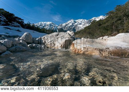 Fresh Mountain River Flowing Over Rocks Through Sunny Evergreen Forest With Last Snow, Mieminger Pla