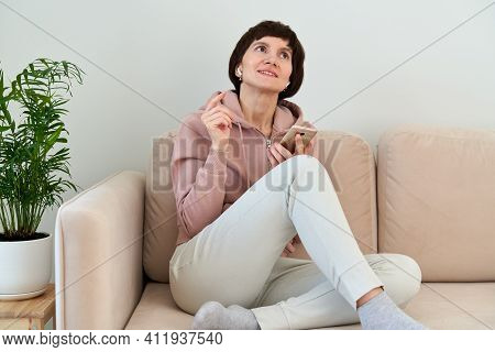 Portrait Of Mature Woman Recording Audio Message, Speaking To Microphone Of Mobile Phone. Middle-age