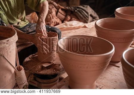 Close Up Hand Of Men Working On The Potter's Wheel. Hands Sculpts A Mortar From Clay Pot. Clay Ware