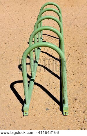 A Green Painted Meta  Bike Rack Throws It\\\'s Shadows On The Concrete.