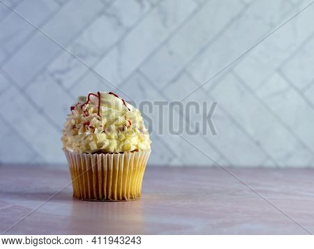 White Cupcake With White Frosting Swirled High And Curled White Chocolate With Red Raspberry Drizzle