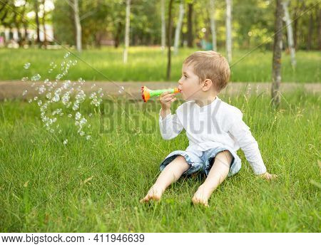 Smiling Funny Child Playing With Soap Bubbles. Happy Little Kid Blowing Soap Bubble In School Garden