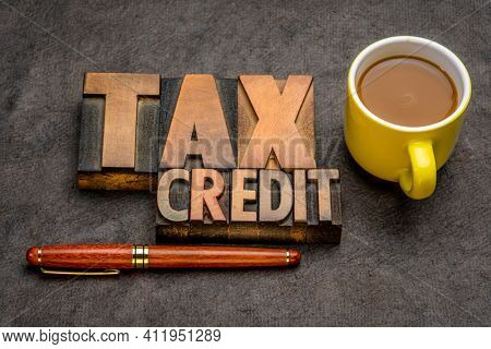 tax credit banner - word abstract in vintage letterpress printing blocks against textured paper with a cup of coffee, business financial concept