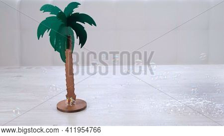 Rtificial Palm Tree And Rainbow Soap Bubbles On A White Wooden Table. Relaxation And Imagination Con