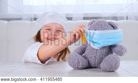 Little Girl Plays A Doctor, Makes An Injection. Happy Child Little Doctor Examines A Teddy Bear. Cor