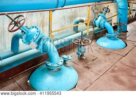 Petrochemical Plant Interior. Two Blue Valves With Brown Red Steering Wheels Over Background Of Pipe