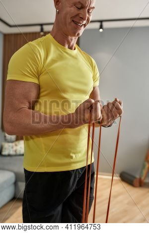 Man Smiling While Exercising At Home With Sports Elastic Band. Coach 49 Years Old Working Out At Hom