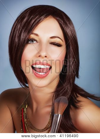 Photo of gorgeous female with perfect makeup isolated on blue background, sexy brunette woman holding in hand brush for blush, playful young lady with open mouth and closed one eyes, beauty concept