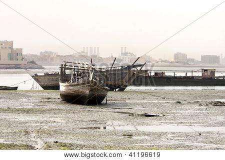 Dhow traditional fishing boat lying on sea bed during low tide
