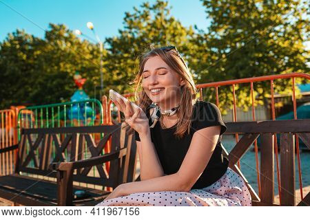 Portrait Of A Happy Woman Sitting On A Park Bench Listening To A Voice Message On Her Smartphone. Th