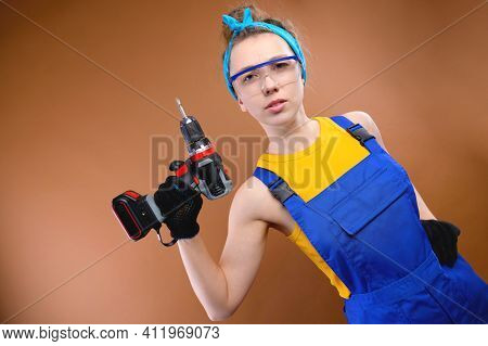 Attractive Harsh Young Woman In Overalls Overalls And Goggles With A Screwdriver In Her Hand On A Br