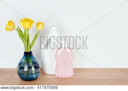 Bottles Of Detergent And Fabric Softener With Yellow Tulip Flowers On Wooden Table. Containers Of Cl