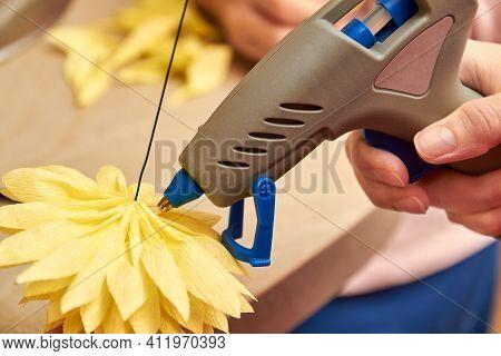 Woman Make Floral Design. Girl Glues The Petals Of An Artificial Flower Using A Glue Gun. Close-up,