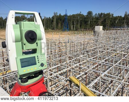 Geodetic Total Station On The Top Of The Bridge Pillar With Scaffolding And Trees In The Background.