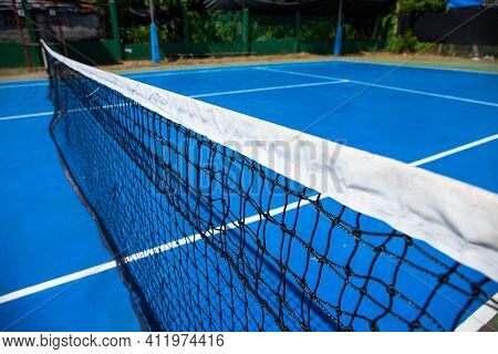 Blue Tennis Court With Net In Park. Empty Sport Field Photo. Hard Cover For Lawn Tennis. Summer Spor