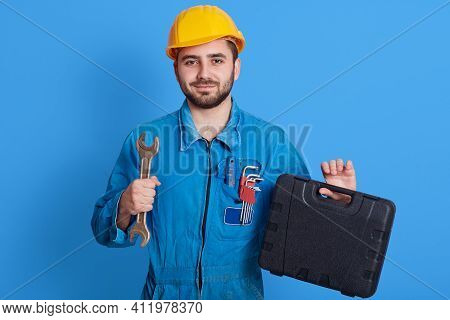 Young Handsome Repairman In Blue Overall And Yellow Helmet Holding Toolbox And Wrench, Bearded Plumb