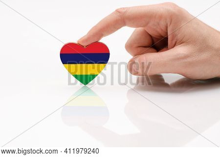 Flag Of The Island Of Mauritius. Love And Respect Mauritius. A Man's Hand Holds A Heart In The Shape