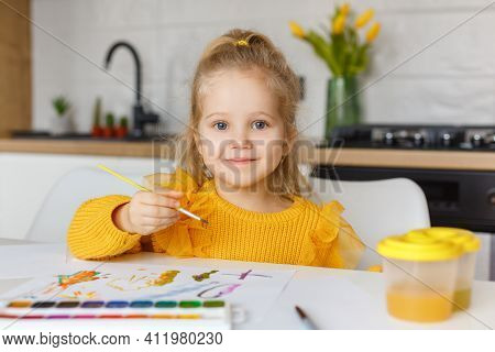Cute Little Girl In Yellow Sweater Painting At Home. Portrait Of 3 Years Old Smiling Kid With Brush