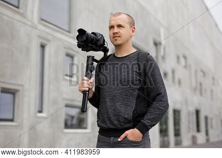 Videography And Creativity Concept - Portrait Of Professional Male Videographer Posing With Dslr Cam