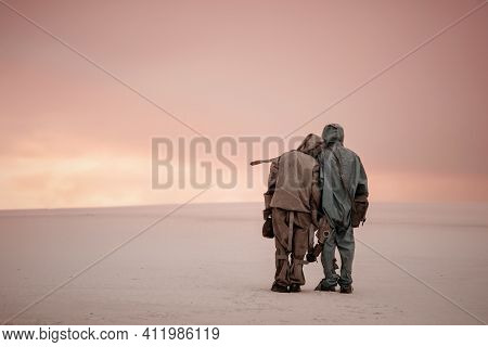 A Man And A Woman In Chemical Protection Suits Stand Side By Side On A Sandy Landscape. In The Hands