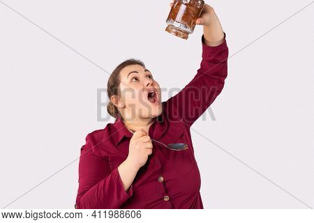 Portrait Of A Chubby Woman With A Spoon And A Large Jar Of Chocolate Paste. Excess Weight From Sweet