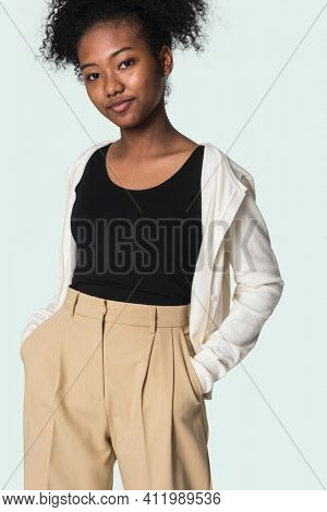 Stylish girl in black tee with beige cardigan and trousers youth fashion shoot