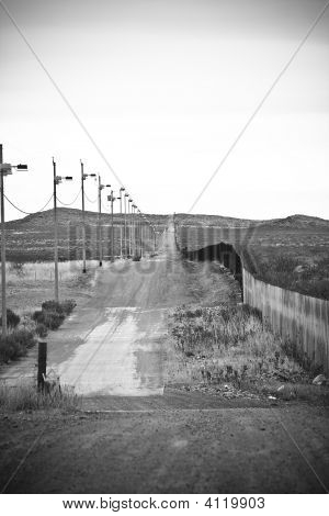 Rural dirt border road between Arizona/US border and Mexico poster