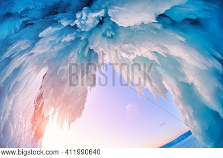 Ice Cave On Baikal Lake In Winter. Blue Ice And Icicles In The Sunset Sunlight. Olkhon Island, Baika