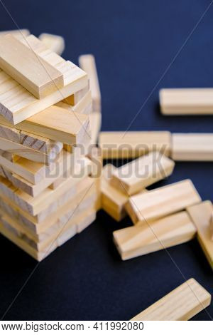 Building From Wooden Blocks - Jenga. Wood Blocks Stack Game With Hand On Background. Conceptual Of T