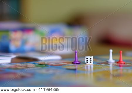 Close Up Of A Board Game With Colored Tokens And A Die