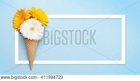 Colorful gerbera flowers in ice cream waffle cone over blue background. Top view flat lay with frame for your text or greetings copy spac