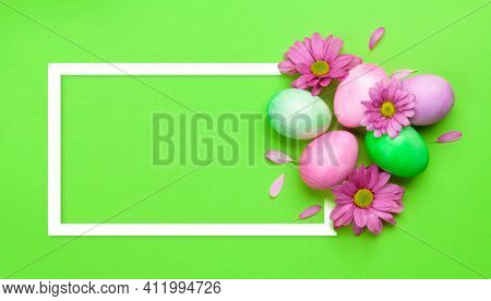 Easter greeting card with colorful easter eggs and flowers. Top view flat lay with frame for your greetings