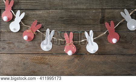 Pom Pom Easter Bunny Craft. Easter Bunny Decoration Paper Cut Background. Diy Holiday Garland Of Col