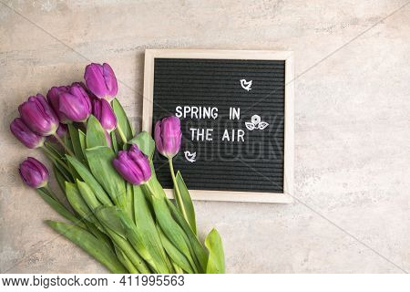 Text  Spring In The Air On  Letter Board And Bouquet Of  Purple Tulips Flowers. Concept Springtime M