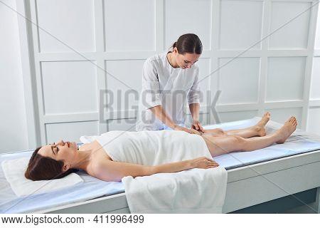 Charming Masseuse Massaging Woman Leg With Medical Massager