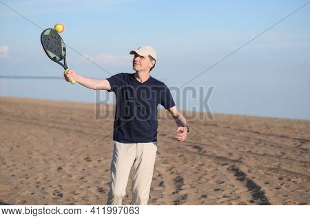 Man in blue t-shirt and white cotton trouses playing beach tennis in sand dunes