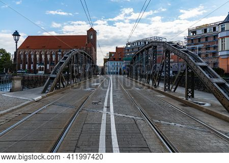 Wroclaw, Poland - May 3 2020: Mlynski Bridge On Island Piasek With Roman Catholic Church Of St. Nmp