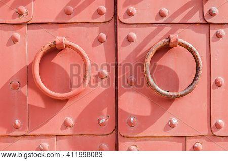 Metal old door with rings door handles and metal rivets.Old door architecture background,old door,iron door,closeup of old door,old door vintage background,old door facade,old door texture,old door view,old door surface