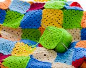Multicolored plaid squares of crocheted. Hook and yarn balls poster