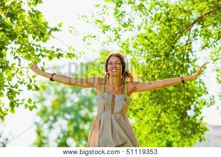 happy girl wearing hedphones outdoors