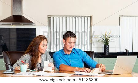 Young couple at the kitchen table, going over their expenses, loans, financial situation and mortgage statements poster