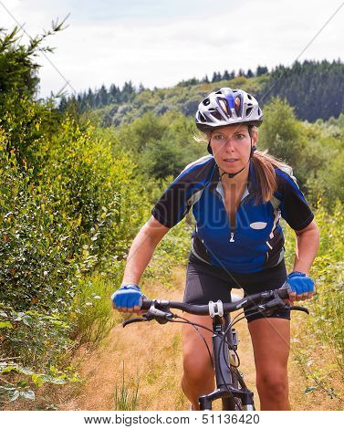 Woman standing on the pedals of her mountain bike, cycling uphill on a small trail