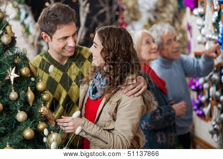 Happy young couple in Christmas store with parents shopping in background