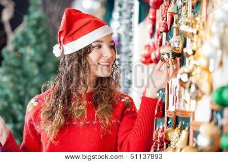 Beautiful woman in Santa hat buying Christmas ornaments at store