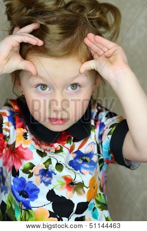 A little girl raised her eyebrows fingers