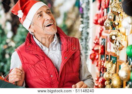 Happy senior man selecting Christmas ornaments at store