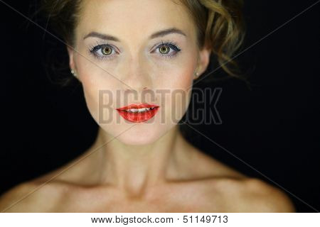 Facial portrait of a young woman with bare shoulders  and ringlight in eyes on a dark background