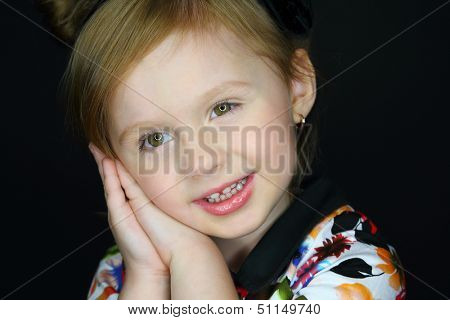 Facial portrait of a smiling little girl with folded hands near the face on a dark background